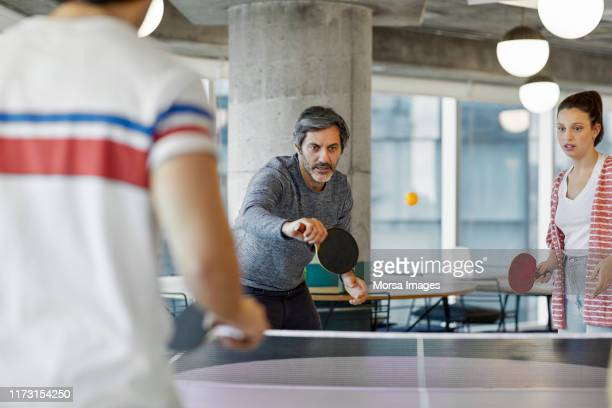 coworkers playing table tennis in office - table tennis stock pictures, royalty-free photos & images