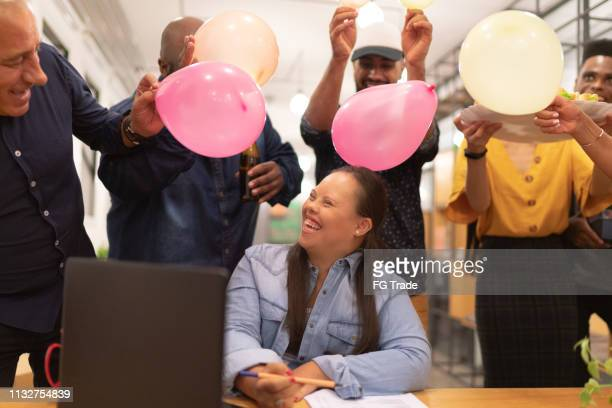 coworkers preparing a birthday surprise for their special needs colleague woman - anniversary stock pictures, royalty-free photos & images