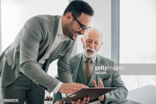 coworkers reading documents - two generation family stock pictures, royalty-free photos & images