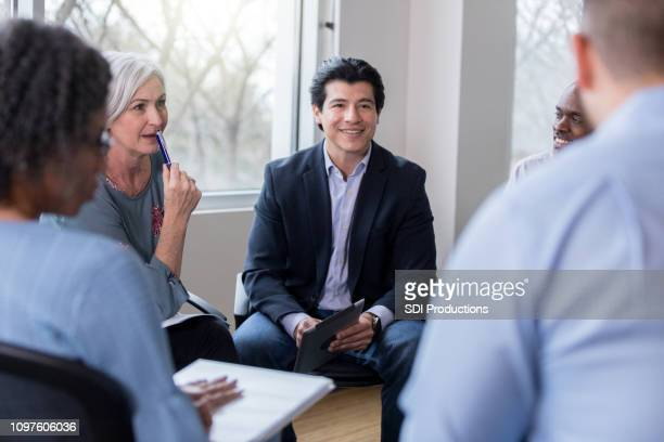 coworkers receive good news during business meeting - mid adult stock pictures, royalty-free photos & images