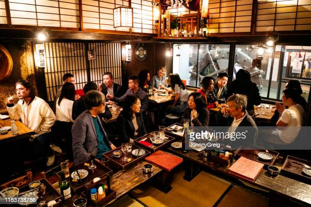 co-workers relaxing in japanese restaurant with food and drink - catering building stock pictures, royalty-free photos & images