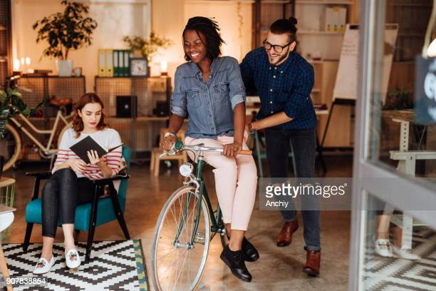 Coworkers riding bicycle and having fun at office