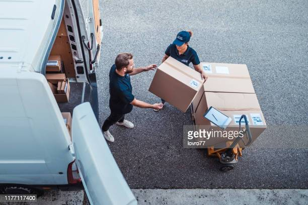 coworkers rushing to load packages in a delivery van - delivery person stock pictures, royalty-free photos & images