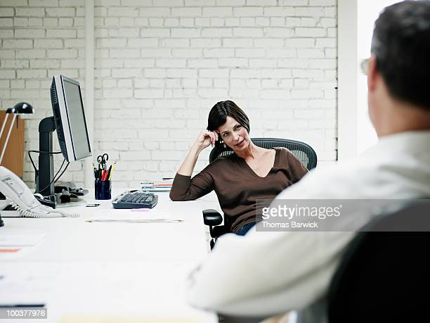 Coworkers seated in discussion at desk in office