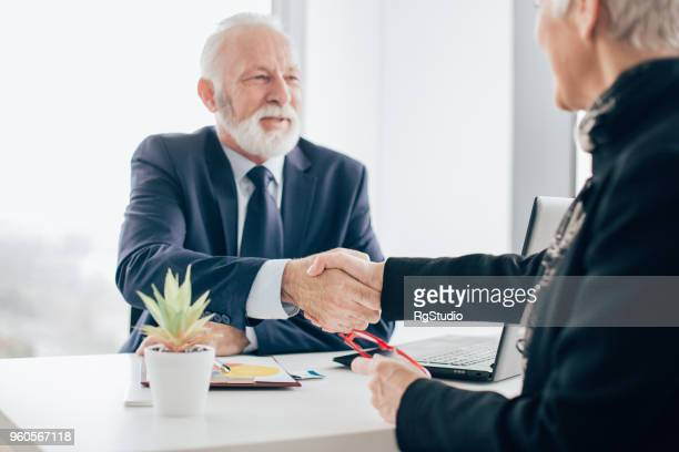 Coworkers shaking hands in office