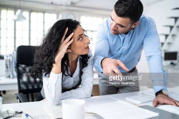 coworkers sitting at workplace and discussing problems - irritation stock pictures, royalty-free photos & images