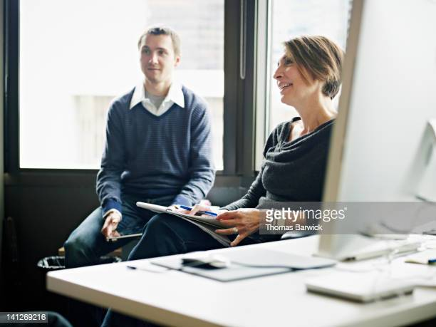 Coworkers sitting listening at office workstation