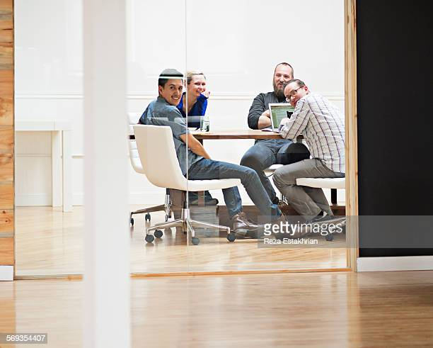 Coworkers smile at colleague outside meeting