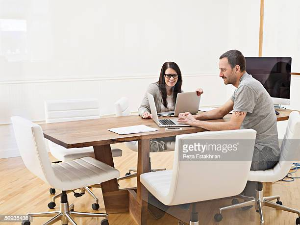coworkers smile over information on laptop - leanintogether stock pictures, royalty-free photos & images