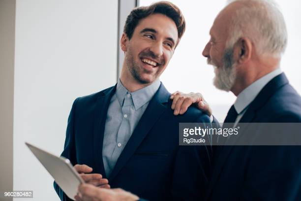 coworkers smiling and holding digital tablet - hand on shoulder stock pictures, royalty-free photos & images
