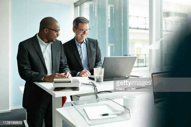 co-workers standing at desk with laptop and talking - ergonomics stock photos and pictures