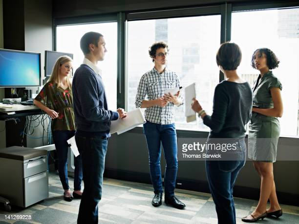 coworkers standing in discussion in office - leanintogether stock pictures, royalty-free photos & images