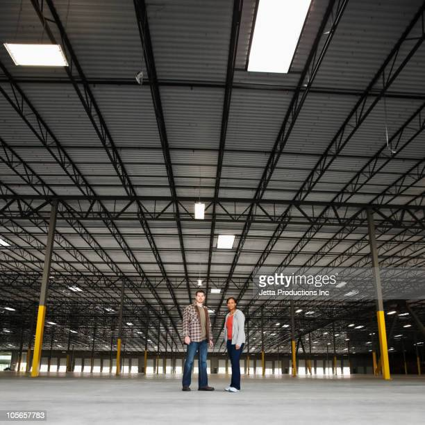Co-workers standing in empty warehouse