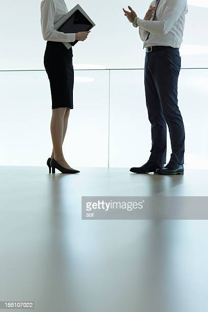 Coworkers standing in office hallway,low section