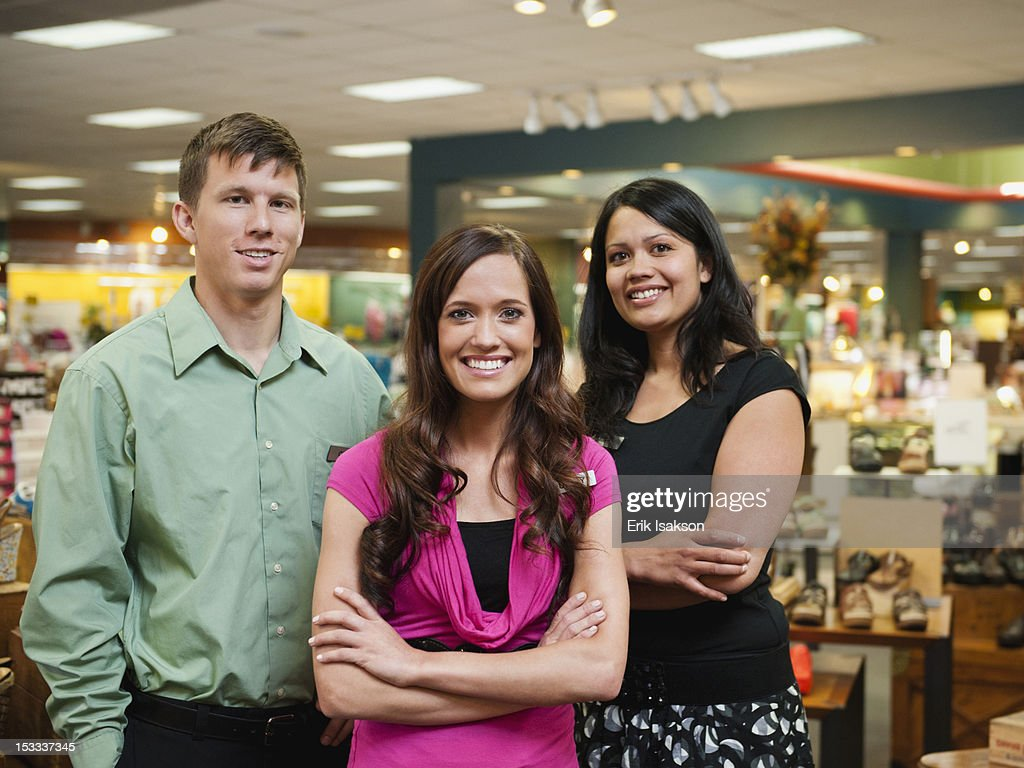 Co-workers standing in store together : Stock Photo