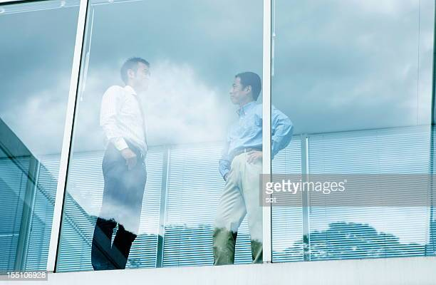 Coworkers standing near windows in office hallway