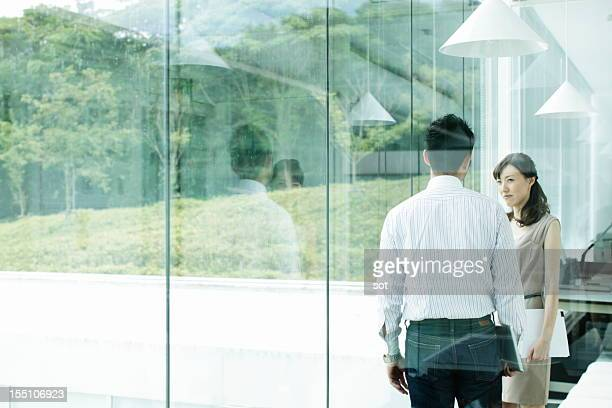 Coworkers standing near windows in office