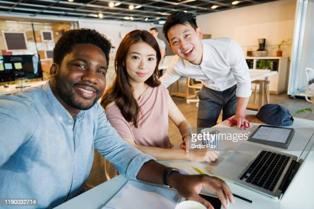 coworkers taking a selfie - small group of people stock pictures, royalty-free photos & images
