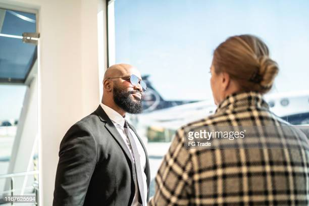 coworkers talking and standing by the window in an airport vip lounge - best sunglasses for bald men stock pictures, royalty-free photos & images