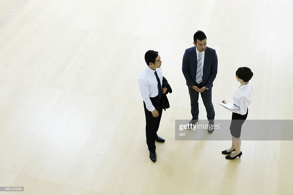 Coworkers talking in entrance hall of office : ストックフォト