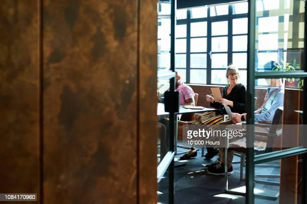 coworkers talking in modern board room - amputee woman stock-fotos und bilder