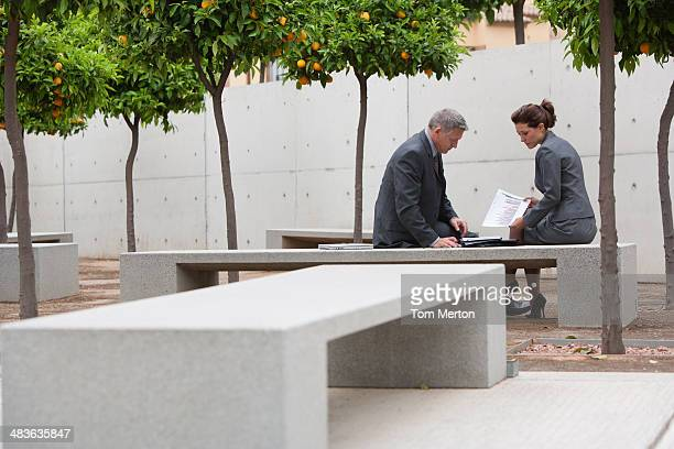 Co-workers talking in office building courtyard