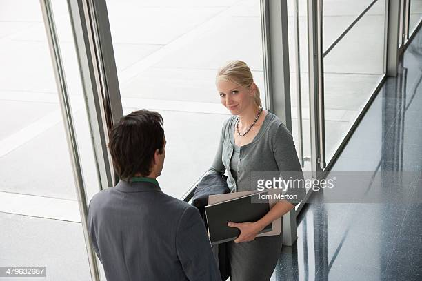 Co-workers talking in office lobby