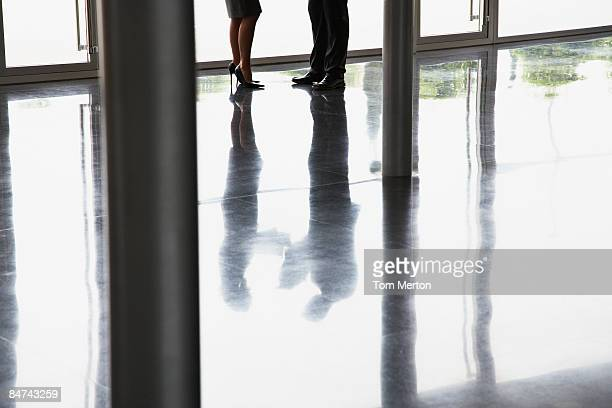 co-workers talking in office lobby - work romance stock pictures, royalty-free photos & images