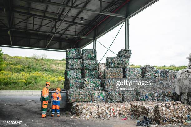 coworkers talking next to stacks of compacted recyclables - waste management stock pictures, royalty-free photos & images