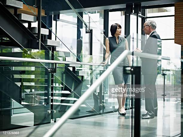 Coworkers talking on office stairway