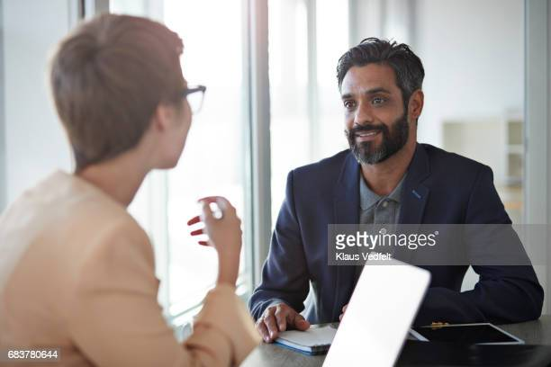 Co-workers talking together at office space