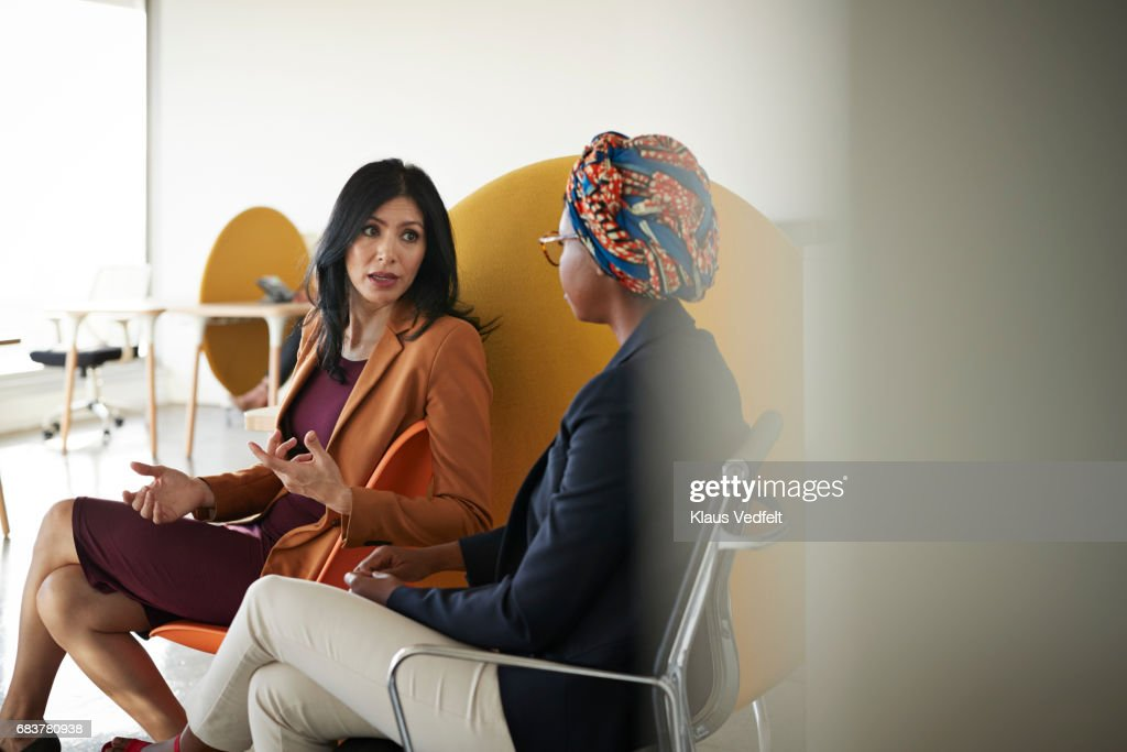 Co-workers talking together at office space : Stock Photo