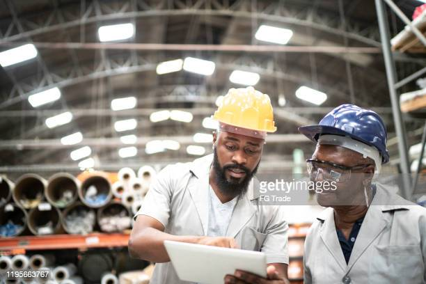 coworkers using digital tablet and working together in a factory - working seniors stock pictures, royalty-free photos & images