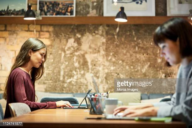 coworkers using laptop in creative office - coworking stock-fotos und bilder