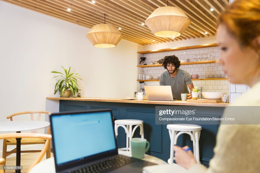 Co-workers using laptop in office kitchen : Stock Photo