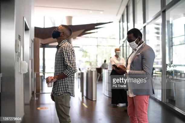 colegas de trabalho esperando elevador no saguão do escritório - com máscara facial - elevador - fotografias e filmes do acervo