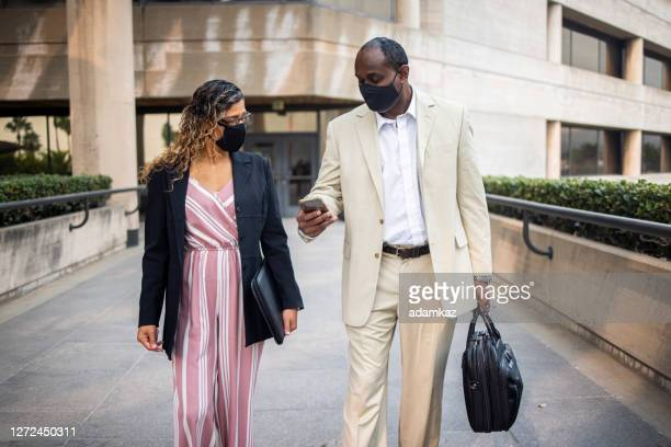 coworkers walking and discussing business - adamkaz stock pictures, royalty-free photos & images
