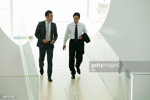 Coworkers walking in entrance hallway of office