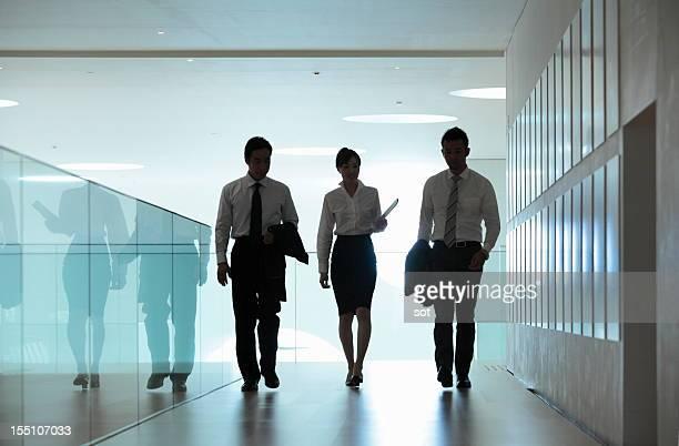 Coworkers walking in office hallway