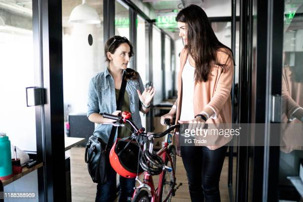 Coworkers walking with bicycle at office corridor