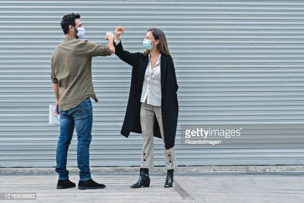 co-workers waving with the elbow taking care of the contagion of covid-19 - elbow bump stock pictures, royalty-free photos & images