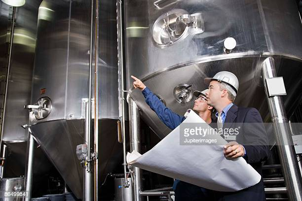 Co-workers with blueprints in a brewery