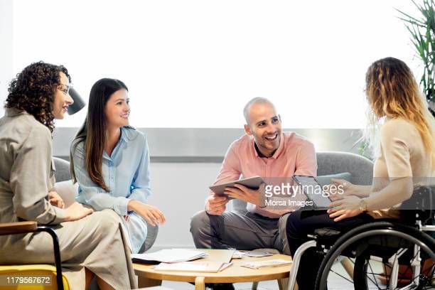 coworkers with disabled businesswoman in office - envolvimento dos funcionários imagens e fotografias de stock