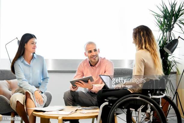 coworkers with disabled female executive in office - disabilitycollection stock-fotos und bilder
