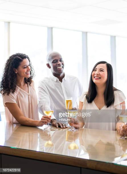 coworkers with drinks celebrating in office - table after party stock pictures, royalty-free photos & images