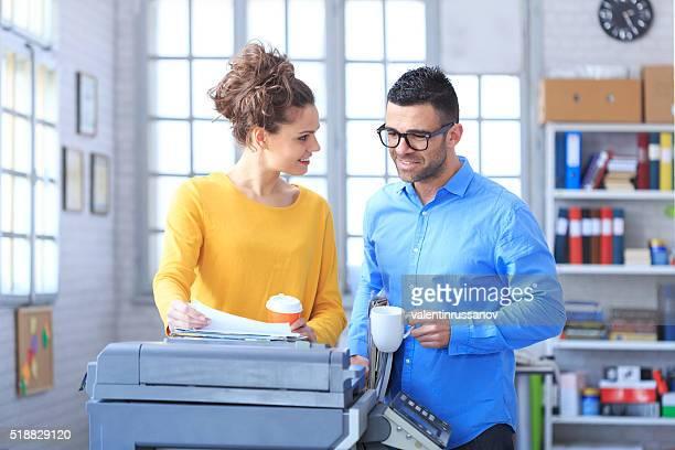 お仕事仲間とコーヒーを飲みながら仕事にオフィス - 印刷機 ストックフォトと画像