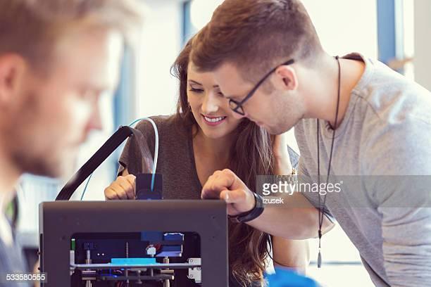 Collègues de travail dans une imprimante 3D au bureau