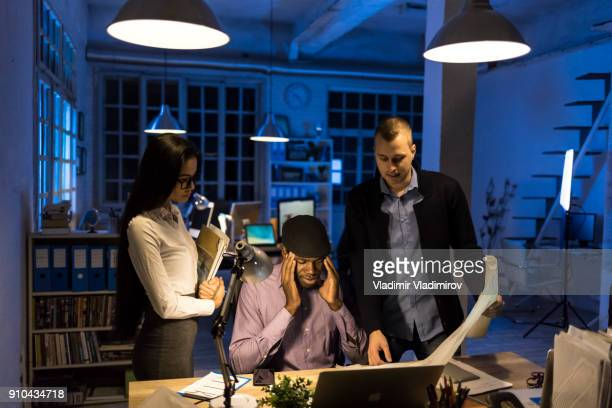 coworkers working late in office - exploitation stock pictures, royalty-free photos & images