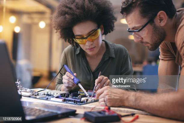 mitarbeiter, die spät an leiteriser neinem büro arbeiten - elektronik industrie stock-fotos und bilder