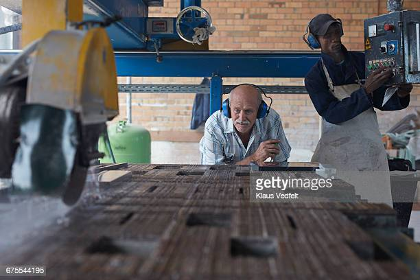 Co-workers working with stone cutting machine